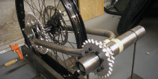 A shot of the rear wheel with the sprocket and the first loop of the swingarm. The wheels are 24″ mountain bike rims with 8″ disc brakes. I had also...